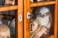 Armário de vidro fechado com bonecas antigas Fotografia de Stock