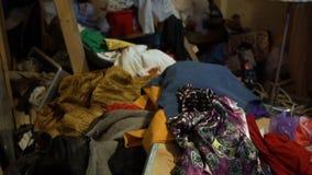 Armário desarrumado com os montões da roupa velha que encontra-se no assoalho e em uma escadaria vídeos de arquivo