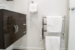 Armário na bacia e na toalha branca nos trilhos do metal para tomar um banho foto de stock royalty free