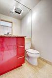 Armário vermelho da vaidade do banheiro com parte superior do granito e o grande espelho Foto de Stock Royalty Free