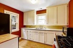 Armários de cozinha brancos com a parede vermelha brilhante Imagem de Stock Royalty Free