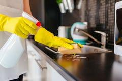 Armários de cozinha da limpeza da mulher com o líquido de limpeza da esponja e do pulverizador