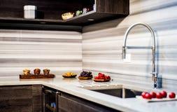 Armários de cozinha de madeira com a bancada branca do granito da cozinha Conceito contrário Fotografia de Stock Royalty Free