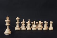Armé av träschackstycken som ledas av konungen på en mörk bakgrund Royaltyfri Foto