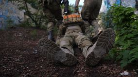Armékommandosoldater som räddar den sårade soldaten från strid arkivfilmer