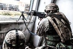 Armémaskinartilleristen anfaller fienden med siktad brand fotografering för bildbyråer