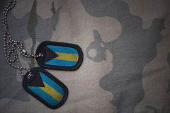 Armémellanrum, hundetikett med flaggan av Bahamas på den kaki- texturbakgrunden Royaltyfria Bilder