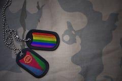 armémellanrum, hundetikett med flaggan av eritrea och den glade regnbågeflaggan på den kaki- texturbakgrunden Royaltyfri Foto