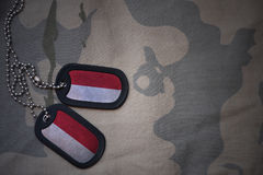 Armémellanrum, hundetikett med flaggan av indonesia på den kaki- texturbakgrunden royaltyfri fotografi