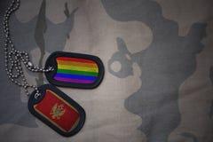 armémellanrum, hundetikett med flaggan av Montenegro och den glade regnbågeflaggan på den kaki- texturbakgrunden Arkivfoton