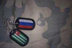 armémellanrum, hundetikett med flaggan av Ryssland och Abchazien på den kaki- texturbakgrunden Royaltyfria Foton