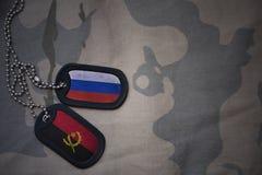 armémellanrum, hundetikett med flaggan av Ryssland och Angola på den kaki- texturbakgrunden Arkivfoton
