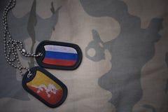 armémellanrum, hundetikett med flaggan av Ryssland och Bhutan på den kaki- texturbakgrunden Arkivfoton
