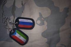 armémellanrum, hundetikett med flaggan av Ryssland och ekvators- guinea på den kaki- texturbakgrunden Royaltyfri Bild