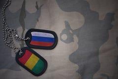 armémellanrum, hundetikett med flaggan av Ryssland och guinea på den kaki- texturbakgrunden Arkivbilder