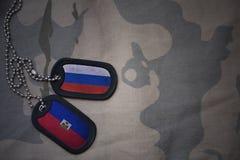 armémellanrum, hundetikett med flaggan av Ryssland och Haiti på den kaki- texturbakgrunden Arkivfoton