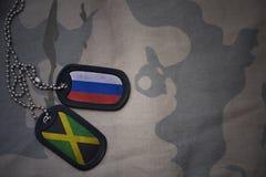 armémellanrum, hundetikett med flaggan av Ryssland och Jamaica på den kaki- texturbakgrunden Royaltyfria Bilder