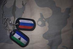 armémellanrum, hundetikett med flaggan av Ryssland och Lesotho på den kaki- texturbakgrunden Royaltyfria Foton