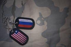 armémellanrum, hundetikett med flaggan av Ryssland och Liberia på den kaki- texturbakgrunden Arkivbilder