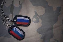 armémellanrum, hundetikett med flaggan av Ryssland och Slovenien på den kaki- texturbakgrunden Royaltyfri Bild