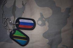 armémellanrum, hundetikett med flaggan av Ryssland och Tanzania på den kaki- texturbakgrunden Royaltyfri Fotografi