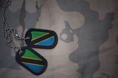 Armémellanrum, hundetikett med flaggan av Tanzania på den kaki- texturbakgrunden Arkivfoton