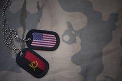 armémellanrum, hundetikett med flaggan av USA och Angola på den kaki- texturbakgrunden Royaltyfri Foto