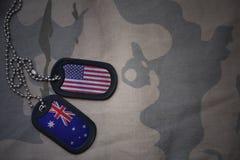 armémellanrum, hundetikett med flaggan av USA och Australien på den kaki- texturbakgrunden Arkivbilder
