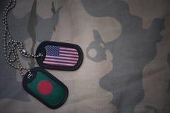 armémellanrum, hundetikett med flaggan av USA och Bangladesh på den kaki- texturbakgrunden Arkivbilder