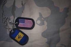 armémellanrum, hundetikett med flaggan av USA och Barbados på den kaki- texturbakgrunden Royaltyfri Foto
