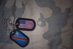 armémellanrum, hundetikett med flaggan av USA och Demokratiska republiken Kongo på den kaki- texturbakgrunden Arkivfoto