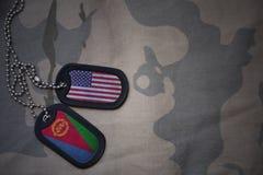 armémellanrum, hundetikett med flaggan av USA och eritrea på den kaki- texturbakgrunden Arkivfoto