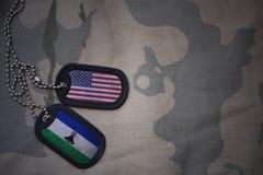 armémellanrum, hundetikett med flaggan av USA och Lesotho på den kaki- texturbakgrunden Fotografering för Bildbyråer