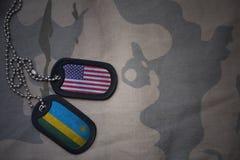 armémellanrum, hundetikett med flaggan av USA och Rwanda på den kaki- texturbakgrunden Royaltyfria Foton