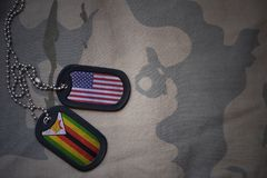 armémellanrum, hundetikett med flaggan av USA och Zimbabwe på den kaki- texturbakgrunden Royaltyfri Bild