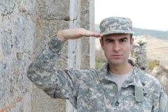 Armésoldaten som saluterar framme av ett ställe fördärvar in royaltyfri foto