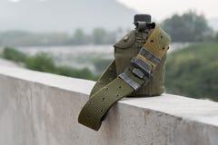 Armévattenkantin med ett kassettbälte på flodstranden Fotografering för Bildbyråer
