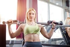 Armübung in der Turnhalle, blondes Mädchen Lizenzfreies Stockbild