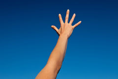 Arm. Outstretched arm of a young woman under blue sky Stock Photo