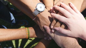 Arm of all races and colors stacked together one by one in unity and teamwork and then raised. Many multiracial hands. Getting together in the center of a stock footage
