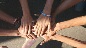 Arm of all races and colors stacked together one by one in unity and teamwork and then raised. Many multiracial hands Royalty Free Stock Photo