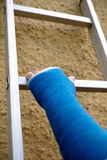 Arm with blue cast on a ladder Royalty Free Stock Image