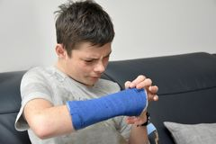 Teenage boy with right arm in plaster stock photos