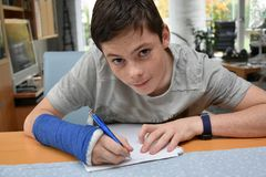 Teenage boy with arm in plaster makes school homework stock photography
