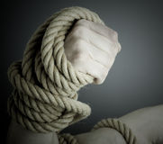 Arm bound with rope. A thick rope wrapped tightly around a man's wrist can imply strength and power or imprisonment and restraint Royalty Free Stock Photo
