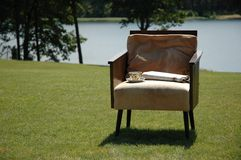 Arm-chair on grass. Arm-chair on with newspaper and coffee cup Royalty Free Stock Images