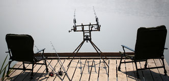 Arm-chairs and fishing rods on wooden pier Stock Photos