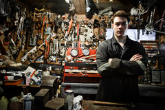 Arm Crossed Worker in a Shed and Lots of Tools Hanging Royalty Free Stock Photos