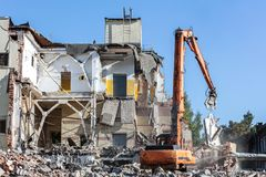Arm of a demolition machine grab part of concrete wall Stock Photography
