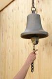 Arm, der eine Bronzeglocke schellt Stockfotografie